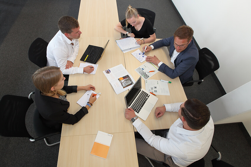 Junge Menschen sitzen um einen Tisch herum, unterhalten sich und arbeiten miteinander.