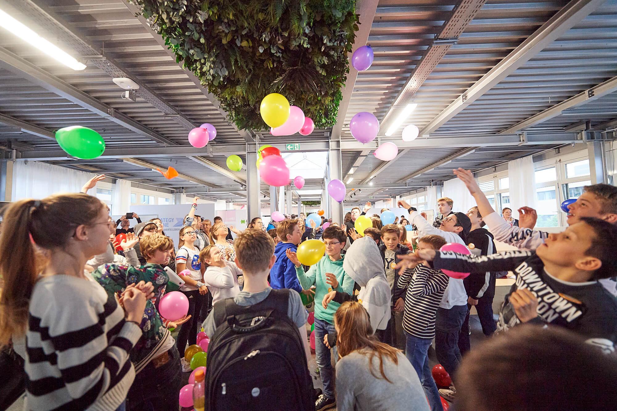 Viele Kinder und Jugendliche schlagen gemeinsam viele bunte Luftballons durch die Luft