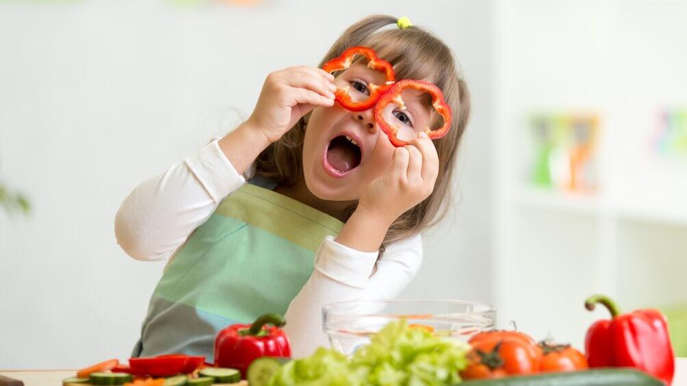 Amapharm: gutgelantes Kind hält sich Paprikaringe vor die Augen