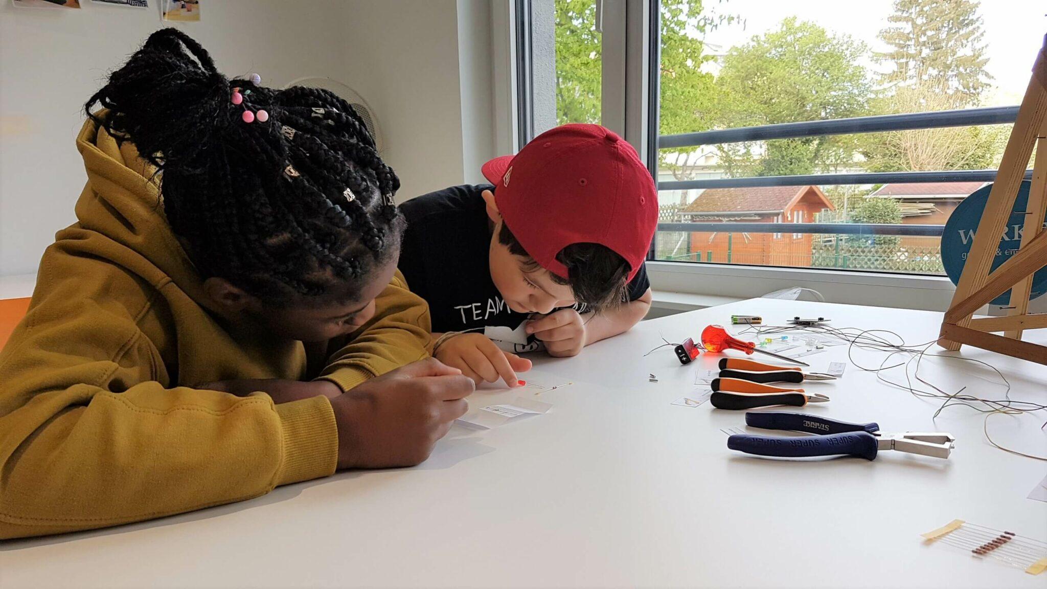 Zwei Kinder beugen sich konzentriert über einen Tisch. Dort liegen Werkzeuge und elektronische Bauteile.